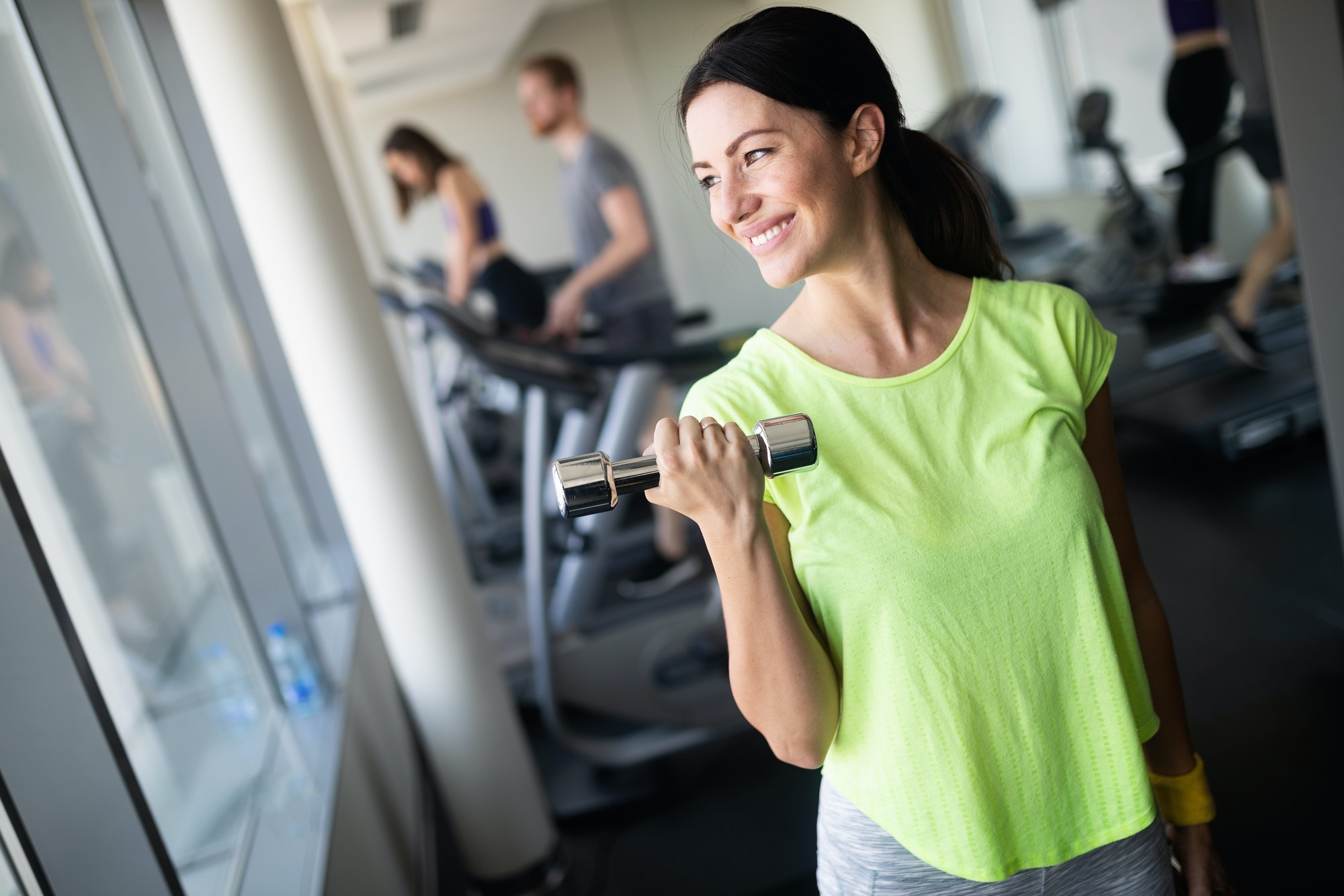 Attractive young woman working out with dumbbells at a gym